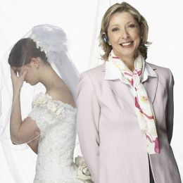 bride with hand covering eyes with smiling mother-in-law