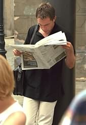 man leaning against wall reading newspaper