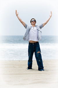 man on seashore with arms outstretched to the sky